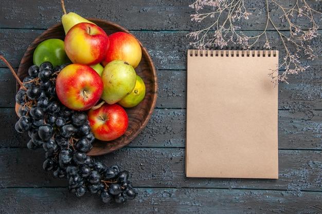 Bovenaanzicht fruit in kom kom druiven peren appels limoenen naast boomtakken en notitieboekje op donkere tafel