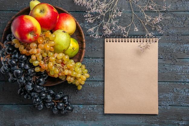 Bovenaanzicht fruit in kom kom met witte en zwarte druiven limoenen appels peren naast crème notebook en boomtakken op grijze ondergrond