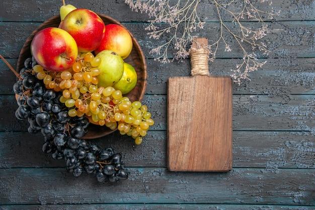 Bovenaanzicht fruit in komkom met witte en zwarte druiven limoenen appels peren naast snijplank en takken op grijze ondergrond