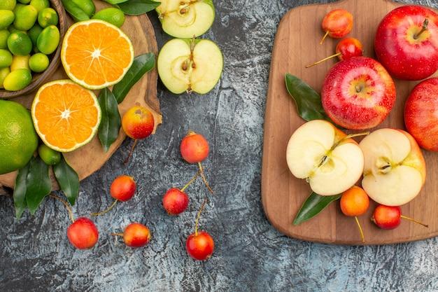 Bovenaanzicht fruit mandarijnen sinaasappelen kersen rode appels op het bord