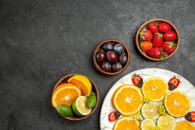 Bovenaanzicht fruit op tafel oranje citroen en met chocolade bedekte aardbeien in witte plaat naast de kommen met bessen en citrusvruchten op het donkere oppervlak