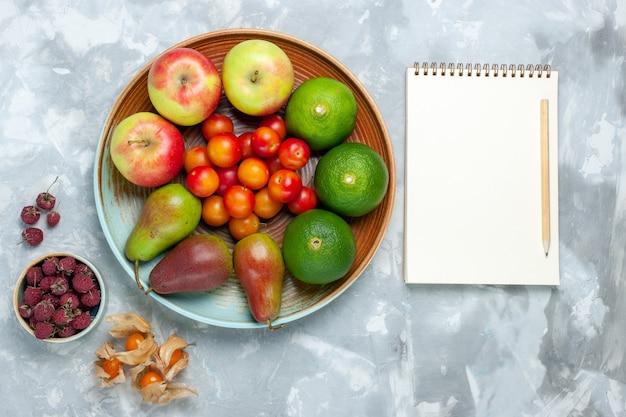Bovenaanzicht fruit samenstelling appels peren mandarijnen en pruimen blocnote op wit bureau.