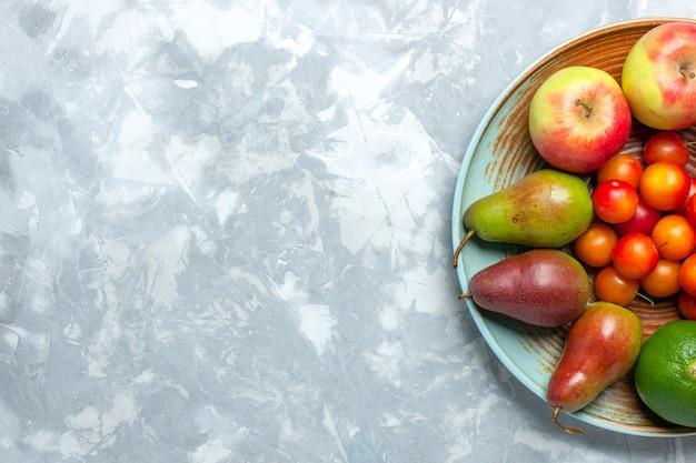 Bovenaanzicht fruit samenstelling appels peren mandarijnen en pruimen op het licht witte bureau.