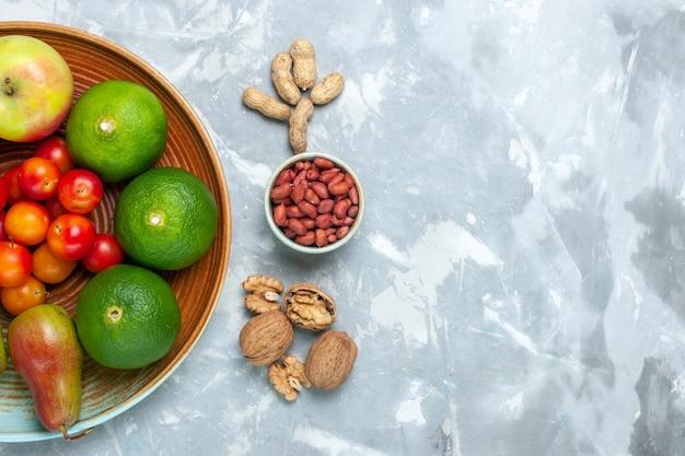 Bovenaanzicht fruit samenstelling appels peren mandarijnen en pruimen op wit bureau.