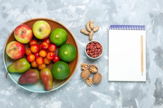 Bovenaanzicht fruit samenstelling appels peren noten mandarijnen en pruimen op het witte bureau.