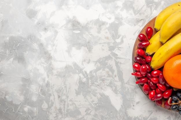Bovenaanzicht fruit samenstelling verse bananen kornoeljes en druiven op wit bureau fruit bes versheid vitamine