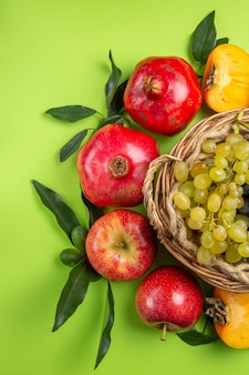 Bovenaanzicht fruitmand met druiventrossen granaatappel appels kaki