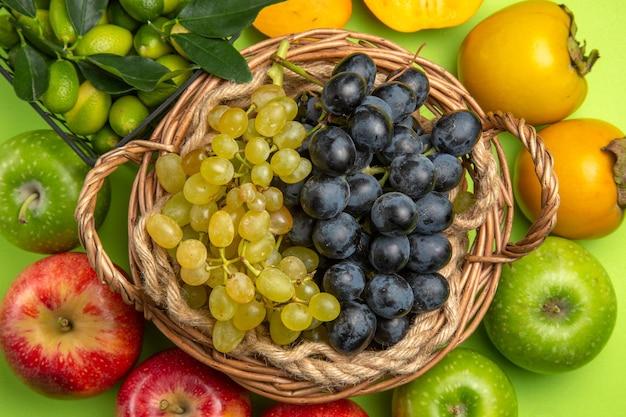 Bovenaanzicht fruitmand met groene en zwarte druiven kaki's appels citrusvruchten