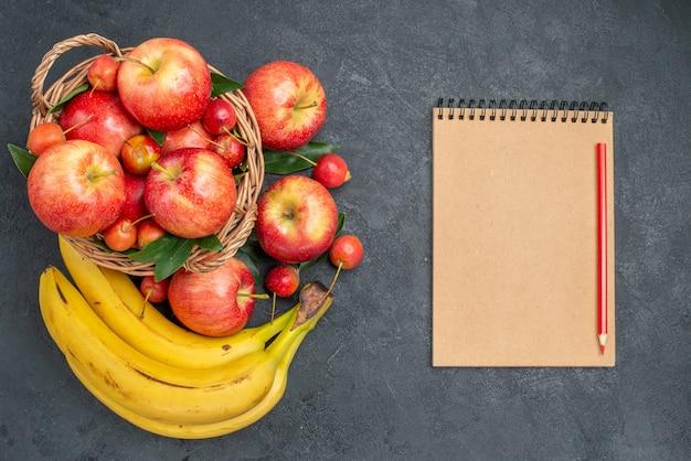 Bovenaanzicht fruitmand met kersen, appels, bananen, notitieboekje potlood