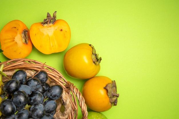 Bovenaanzicht fruitmand met zwarte druiven de smakelijke dadelpruimen op de groene achtergrond