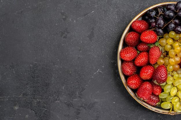 Bovenaanzicht fruitsamenstelling aardbeien druiven frambozen en mandarijnen in lade op donker bureau