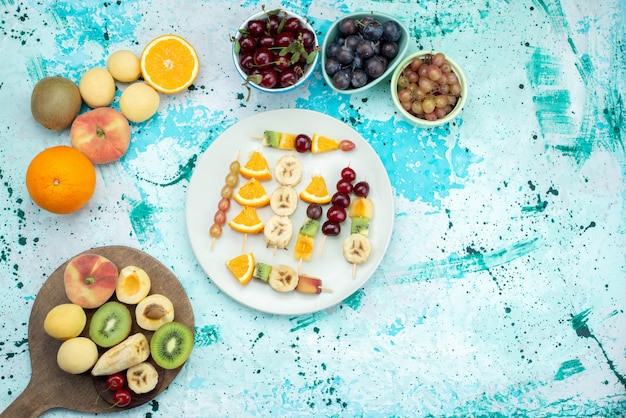 Bovenaanzicht fruitsamenstelling gesneden en geheel op de exotische koekjessuiker van het blauwe bureau