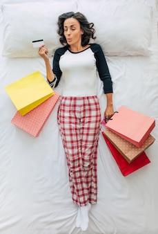 Bovenaanzicht full-length foto van een mooie jonge krullende brunette vrouw in casual kleding met boodschappentassen en creditcard in handen. dromen over winkelen in een winkelcentrum. zwarte vrijdag