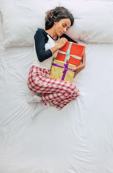 Bovenaanzicht full-length foto van een mooie jonge krullende brunette vrouw in casual kleding met geschenkdozen in handen. dromen en ontspannen