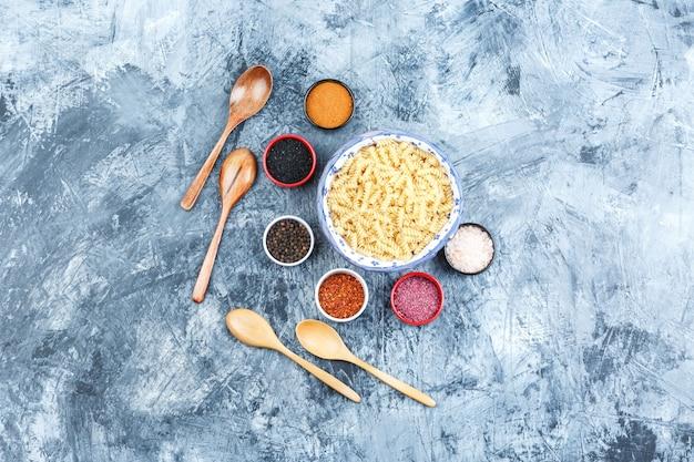 Bovenaanzicht fusilli pasta in kom met kruiden, houten lepels op grijze gips achtergrond. horizontaal