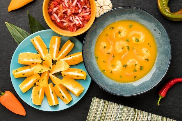 Bovenaanzicht garnalensoep en stukjes sinaasappel