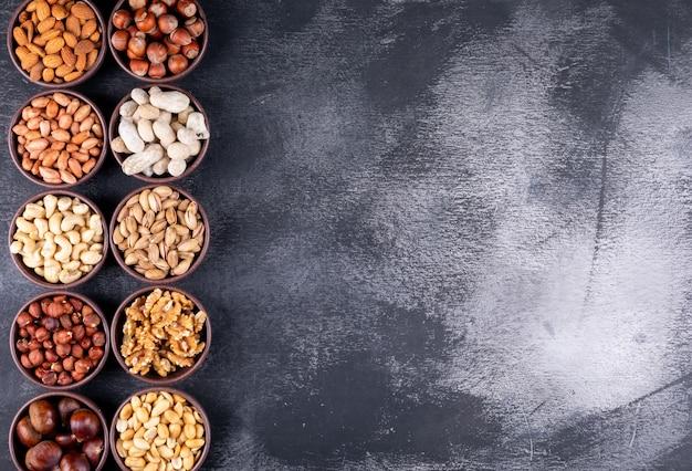 Bovenaanzicht geassorteerde noten en gedroogde vruchten in verschillende mini-kommen met pecannoten, pistachenoten, amandel, pinda