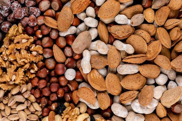 Bovenaanzicht geassorteerde noten en gedroogde vruchten met pecannoten, pistachenoten, amandel, pinda's, cashewnoten, pijnboompitten. horizontaal