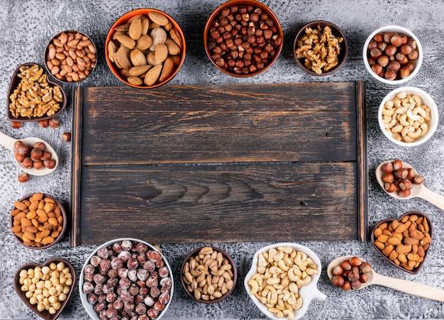 Bovenaanzicht geassorteerde noten in verschillende mini kommen met donkere houten plank