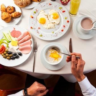 Bovenaanzicht geassorteerde ontbijt met havermout en gebakken eieren, menselijke hand in witte plaat