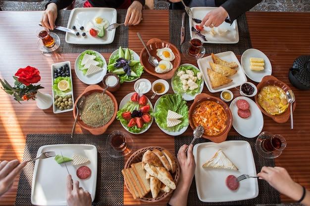 Bovenaanzicht geassorteerde ontbijt met omelet en glas thee en handen van mensen in servetten
