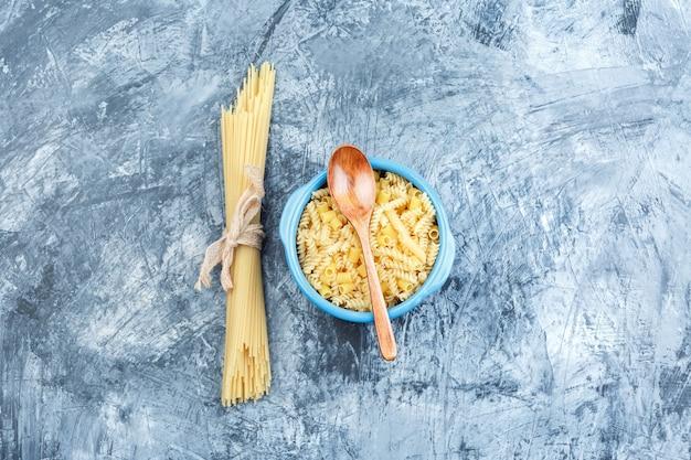 Bovenaanzicht geassorteerde pasta in kom met houten lepel op grijze gips achtergrond. horizontaal