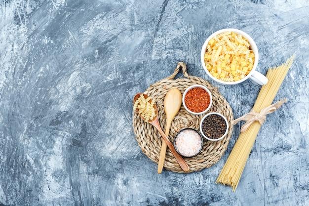 Bovenaanzicht geassorteerde pasta in kom met houten lepels, kruiden op grijze gips