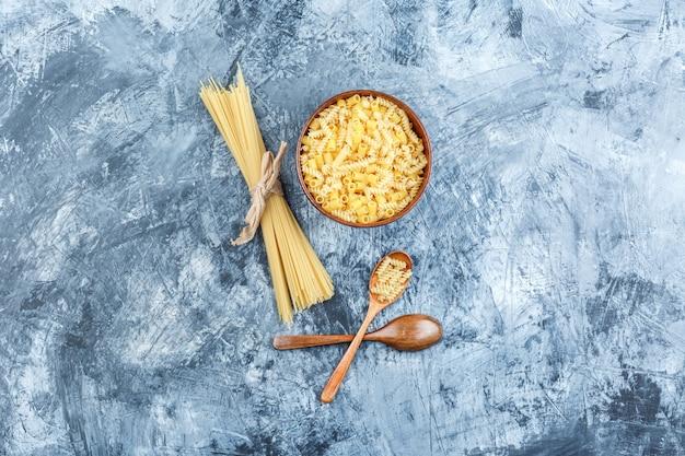 Bovenaanzicht geassorteerde pasta in kom met houten lepels op grijze gips achtergrond. horizontaal