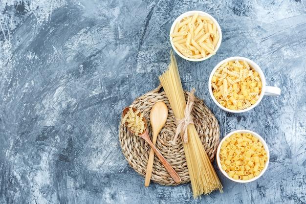 Bovenaanzicht geassorteerde pasta in kommen met houten lepels op grijze gips en rieten placemat achtergrond. horizontaal