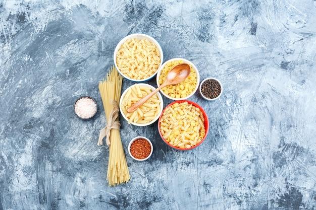 Bovenaanzicht geassorteerde pasta in kommen met kruiden, houten lepel op grijze gips achtergrond. horizontaal