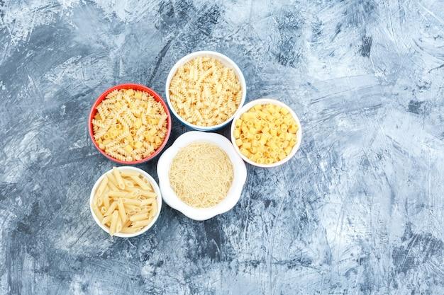 Bovenaanzicht geassorteerde pasta in kommen op grijze gips achtergrond. horizontaal
