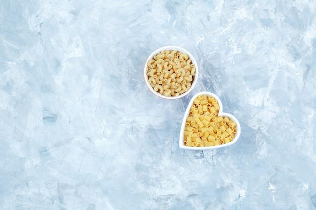 Bovenaanzicht geassorteerde pasta in kommen op grungy grijze achtergrond. horizontaal