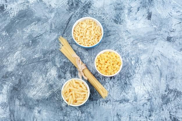 Bovenaanzicht geassorteerde pasta in witte kommen op grijze gips achtergrond. horizontaal