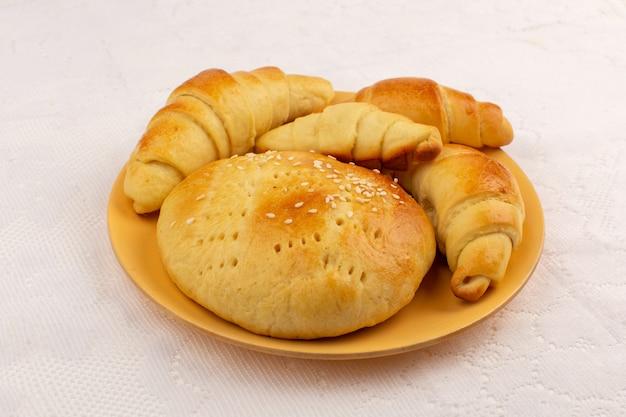 Bovenaanzicht gebak en croissants in oranje plaat op de witte vloer