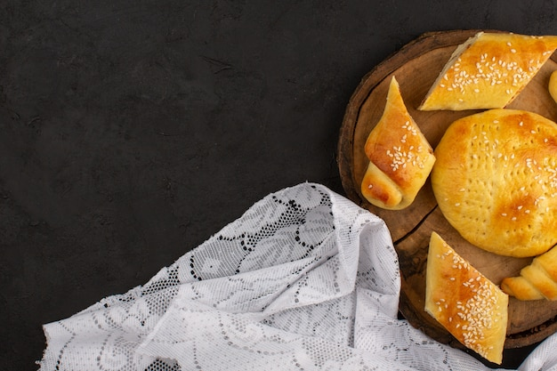 Bovenaanzicht gebak en croissants op de bruin houten bureau en donkere achtergrond