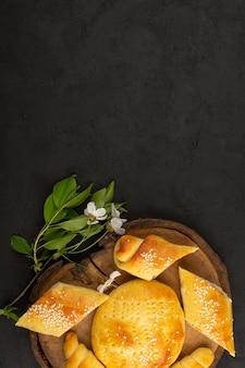 Bovenaanzicht gebak en croissants op de donkere achtergrond