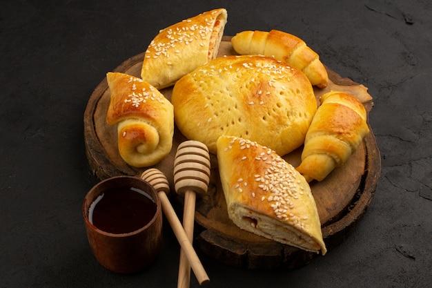 Bovenaanzicht gebak en croissants op het bruine bureau en de donkere achtergrond
