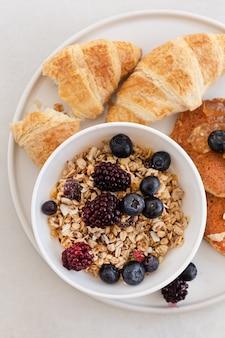 Bovenaanzicht gebak producten in lade met olijven, frambozen en noten op witte tafel. verticaal