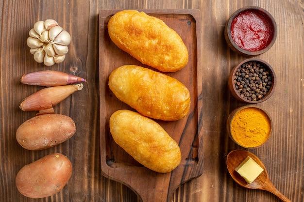 Bovenaanzicht gebakken aardappel hotcakes met smaakmakers op een bruin houten bureau cake bakdeeg aardappelmeel oven