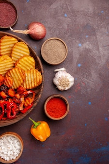 Bovenaanzicht gebakken aardappelen met gekookte groenten op donkere ruimte