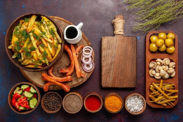 Bovenaanzicht gebakken aardappelen met kruidenbrood en verschillende groenten op het donkere oppervlak