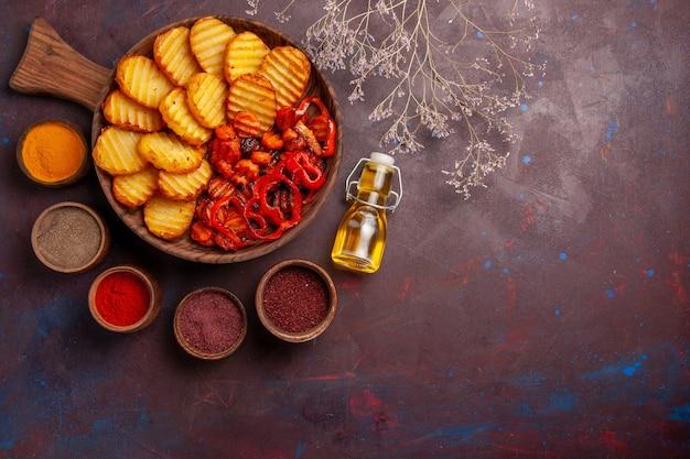 Bovenaanzicht gebakken aardappelen met verschillende kruiden op de donkere ruimte