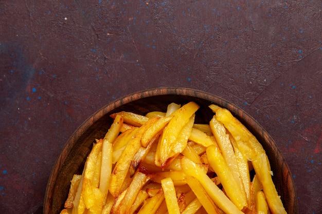 Bovenaanzicht gebakken aardappelen smakelijke frietjes in plaat op donkere ondergrond voedsel maaltijd diner schotel ingrediënten aardappel