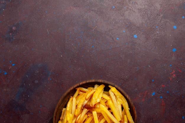Bovenaanzicht gebakken aardappelen smakelijke frietjes in plaat op het donkere oppervlak