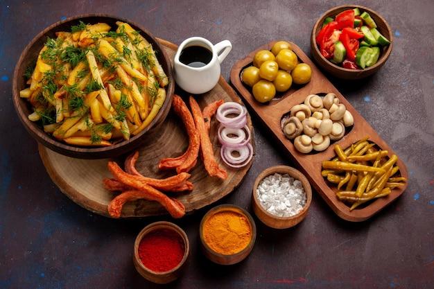 Bovenaanzicht gebakken aardappelen smakelijke frietjes met worstjes en verschillende smaakmakers op het donkere bureau