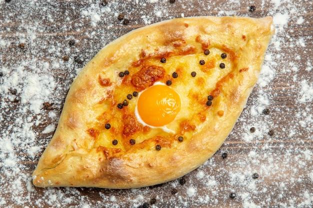 Bovenaanzicht gebakken brood met gekookt ei en bloem op bruin bureau deeg bakken eieren brood broodje