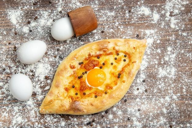 Bovenaanzicht gebakken brood met gekookt ei en bloem op het bruine bureau deeg ei brood broodje ontbijt