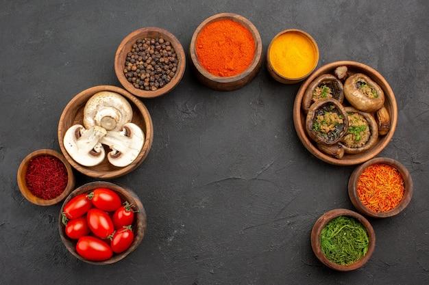 Bovenaanzicht gebakken champignons met tomaten en kruiden op donkere achtergrond