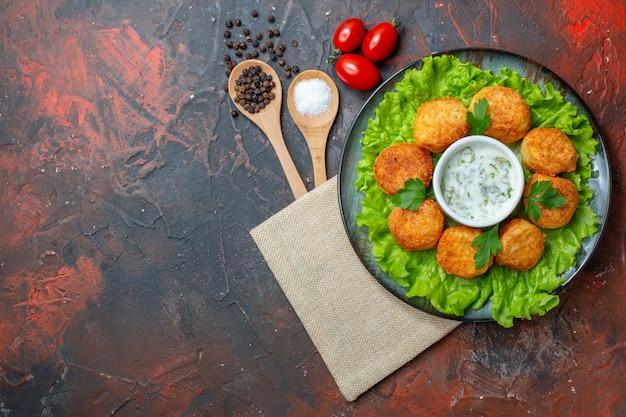 Bovenaanzicht gebakken cheee ballen sla op plaat cherry tomaten zout en zwarte peper in houten lepels op donkere tafel vrije ruimte