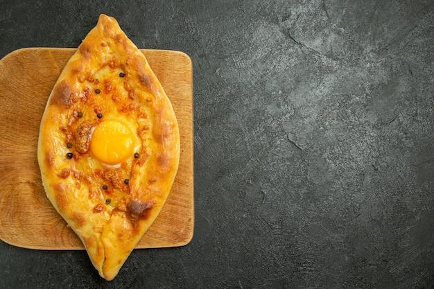 Bovenaanzicht gebakken eierbrood heerlijk deegbroodje vers uit de oven op donkere ruimte